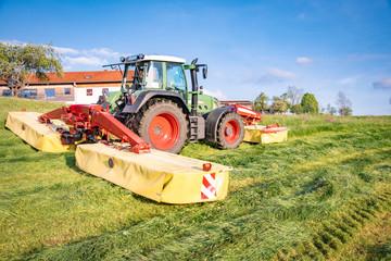 Fototapete - Moderne Landtechnik  im Einsatz - Traktor mit Kreiselmähern beim Gras mähen