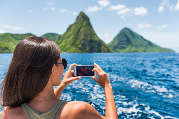 Wall Mural - Cruise boat tourist taking mobile phone pictures of Deux pitons peaks, St-Lucia, Caribbean. The Gros and Petit Piton, world heritage site. Woman on shore excursion from ship in Castries, port of call.