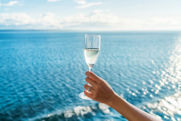 Wall Mural - Champagne glass woman's hand toasting on ocean background at luxury cruise ship during sunset. Travel vacation for honeymoon, lady holding flute wearing wedding ring.