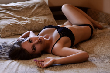 Young and sexy girl in black underwear lies on the bed