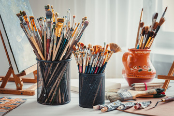 Artistic equipment: easel,  paintbrushes, tubes of paint, palette and paintings on work table in a artist studio.