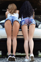 Rear view of two young girls in blue short denim shorts is repairing the car