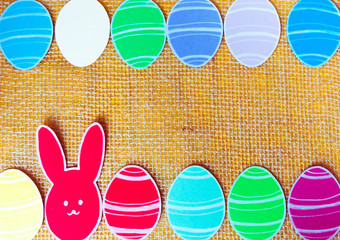 Close-up of colorful paper rabbits and paper eggs silhouette frames against canvas background
