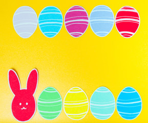 Close-up of colorful paper rabbit and paper eggs silhouette frames against canvas background