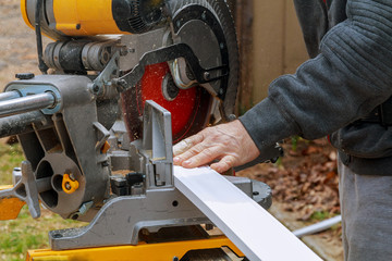 Side view of mid adult manual worker cutting wood