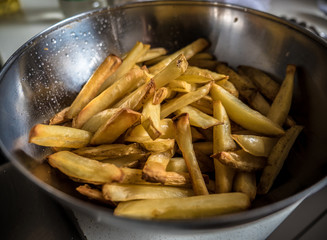 Silver cooking bowl full of homemade potato fries straight out of the oven