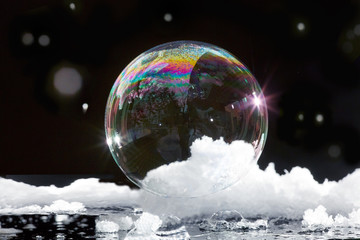 Ice bubble with rainbow colors floating in snow