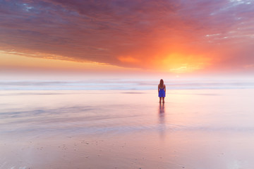 A silhouetted woman watches a beautiful sunrise over the ocean on Australia.