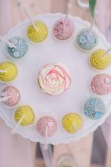 Rosa Cupcake umrahmt von Cakepops süßer bunter Teller