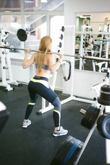 girl in bright white gym. Athletic slender sexy blonde woman doing strength exercise for group of leg muscles and buttocks squatting with lightweight barbell barb. Healthy way of life, good spirits