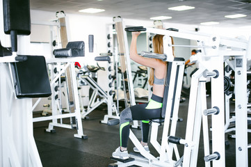 girl in a bright white gym. A blonde woman doing a strength exercise for a group of muscles on the hands of a simulator. Healthy way of life, good spirits