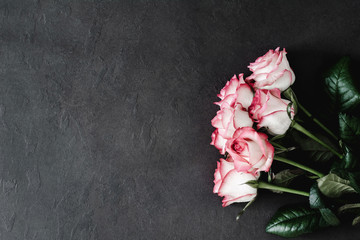 Floral frame: bouquet of pink and white roses on dark stone background with copy space for text. Styled womans day, mothers day floral background