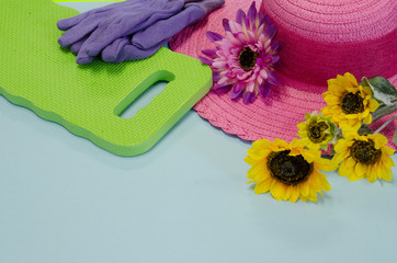 A pink hat, kneeling pad and gardening gloves with sunflowers on a light blue background with copy space