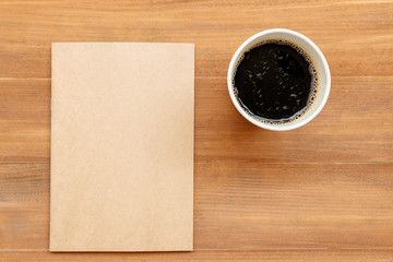 blank cover book and cup of coffee on brown wooden background