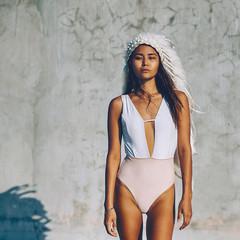Beautiful female model in bodywear and federschmuck on summer beach