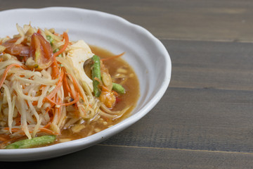 Thai spicy papaya salad on wooden table