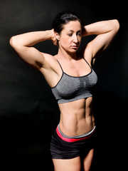 Muscular female belly over black