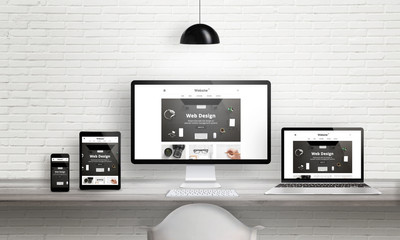 Fototapeta Creative web design agency presentation on multiple devices. Computer display, laptop, tablet, smart phone on white wooden desk. Brick white wall in background. obraz