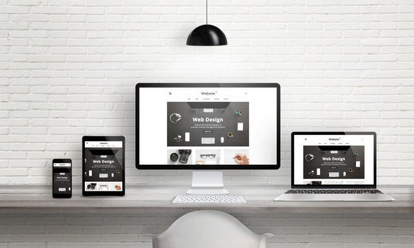 Creative web design agency presentation on multiple devices. Computer display, laptop, tablet, smart phone on white wooden desk. Brick white wall in background.