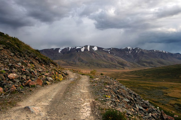 Extreme rocky road in a mountain valley to the pass in cloudy weather on the background of snowy mountain ranges Plateau Ukok Altai Siberia Russia