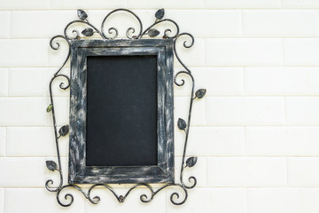 Antique picture frame hanging on a white wall.