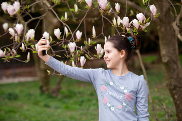 Young girl making selfie in the spring park