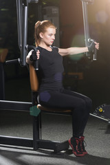 Woman at the sport gym doing arms exercises on a machine. Dark sport club.