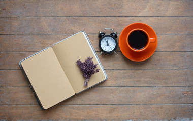 photo of opened notebook, bunch of lavender, alarm clock and cup of coffee on the wonderful wooden brown background