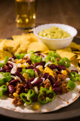 Closeup of Mexican tortillas with meat, red beans, Jalapeno pepper, nachos chips, beer and salsa guacamole