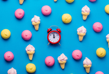 photo of tasty colorful marshmallows and alarm clock on the wonderful blue background