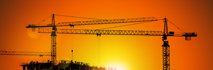 Tower cranes and building silhouette with workers at sunrise.