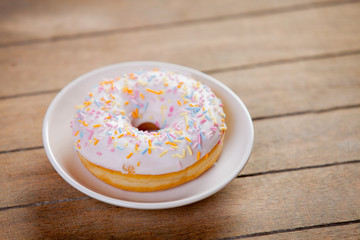 photo of tasty donut on plate on the wonderful brown wooden background