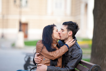 photo of cute couple sitting on the bench and kissing on the wonderful park background