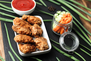 Parts of chicken wings in breading with tomato sauce on black shale plate
