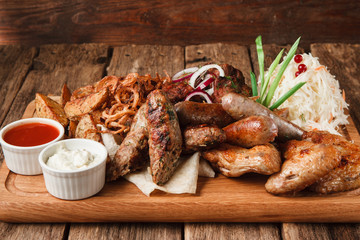 Delicious snacks for beer served with pita bread, fried potato wedges,onion rings and sauerkraut on rustic wooden table. Restaurant menu photo.