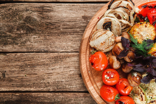 Wooden platter with grilled vegetables on rustic wooden table, top view. Free space for text. Restaurant menu photo. Healthy lifestyle, vegetarian cuisine concept