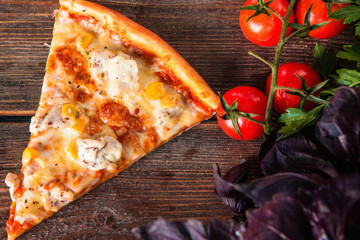Slice of delicious italian pizza served on wooden table with cherry tomatoes, parsley and basil, top view.