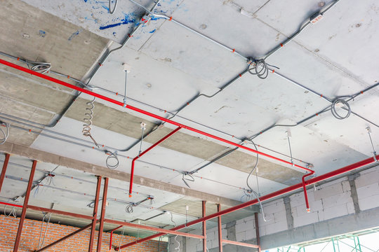 Ventilation pipes in black insulation material and fire sprinkler on red pipe are hanging from the ceiling inside new building.