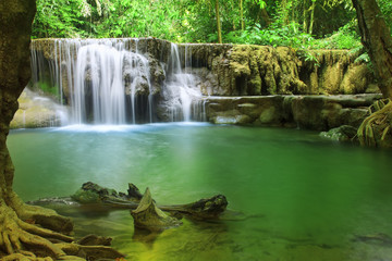 waterfall left side with clear green emerald water and rock for relax and refreshing cool with tree and root in the jungle or forest at Huay Mae Khamin waterfall for nature landscape and background