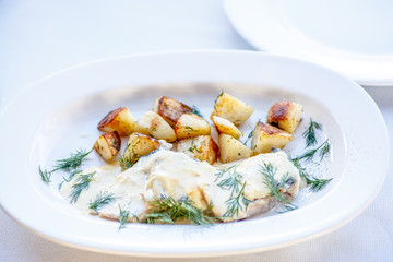 Fish in white sauce with fried potatoes.
