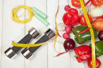 Sport and diet. Healthy lifestyle. Vegetables, dumbbells. Peppers, tomatoes, garlic, onions radishes on a white background