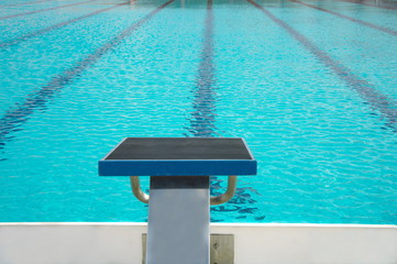 start up block with lane of water in  blue swimming pool