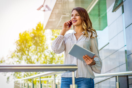 Business woman holding tablet pc computer and calling on cell phone outside corporate building.