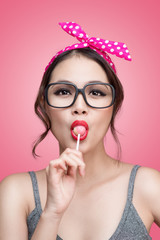 Portrait of beautiful asian woman eating heart shape lollipop, dressed and makeup in pin-up style on pink background.