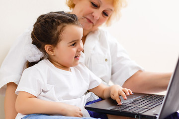 cheerful little girl and grandma using laptop computer at home