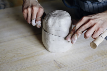 Woman hands close-up, forming crude clay in a potter's workshop studio. Craft-work