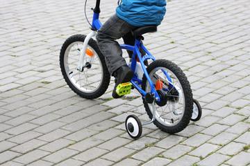 A boy rides on a bike.