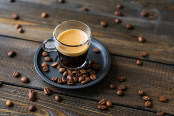 A cup of espresso and coffee beans on a wooden table