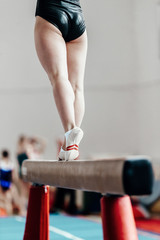 back part of body female gymnast exercises on balance beam