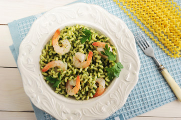 pasta with shrimp and spinach in a bowl and ingredients for cooking pasta